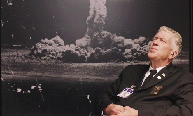 Gordon Cole leans back in his office chair whistling in front of a picture of the Los Alamos A-bomb test