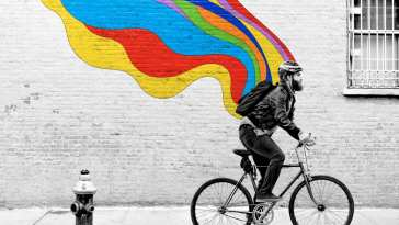 The Guy on a bike with a rainbow mural behind him
