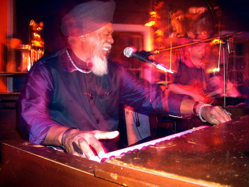 """New York based organist and pianist Dr. Lonnie Smith (b. 1942), who converted into Sikhism in the mid 1970s. Here, Lonnie rocks the piano while sporting a matching navy blue turban and silk kurta, with his kara, necklace, and bracelets on his right arm."""