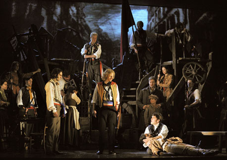 Barricade scene from Les Mis.  Enjolras stands in the center in a bright red and gold vest.