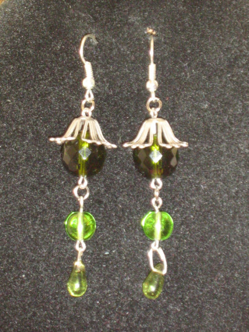Silver tone bead cap, with green Czech glass beads (cut and polished), silver plate pins and fish hook ear wires.Dainty delicate dangling earrings in soft woodland colours, perfect for spring evenings. They should sway beautifully with every shake of your head, just like the leaves of trees.<br />Click on image for listing