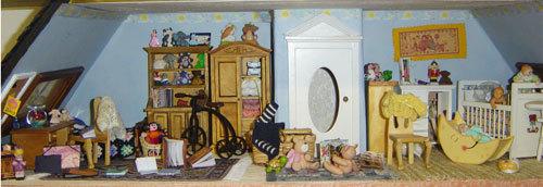 EL ATICO En la buhardilla aun quedan muchas cosas por hacer…Será la habitación de los niños y quiero darle un aire mas actual y divertido. donde pondré poner muchas estanterías con juguetes realizados por mi, casitas de muñecas, juegos, cuentos, etc.La persiana esta hecha con un calendario de un chino. (Los muebles los compre en un mercadillo muy baratos y aunque son de una escala ligeramente inferior en el ático no se nota mucho por que el techo es mas bajo y como son para los niños puede justificar que sean más pequeños.) Losmuebles de bebefueron un regalo de mi sobrina y los voy a dejar así, por que son muy bonitos. Los niños tendrán una enorme mesa sobre la que jugar merendar y hacer fiestas. Muchas e las cosas de la buardilla son regalos de los participantes del grupocasa de muñecas Perdonad si no he puesto todos los nombres. Elcorchoes regalo de Nina yla muñequitade Karina. Sobre la camita podemos ver una ropita regalo de Carolina de Venezuela junto a la telita para los edredones. Sobre la estantería podemos ver un osito de fimo hecho por mi y otro hecho por carmen (Tuporaki) Sobre la alfombra roja (regalo de Mary de Tenerife) podemos ver una muestra de juguetes de los huevos kindder. El bebe con lacuna de lunaesta hecho en fimo por Rosa23.. Al lado de la casita de muñecas tengo una preciosa muñeca regalo de Arancha(edurne) y dos ositos uno de Flor de Mexico y otro de Carmen.Laalfombrade pachwork regalo de Susan del grupo de miniaturas. Sobre la mesa del escritorio tengo algunos de mis tesoros favoritos. Una preciosidad de minivestido que compré en una feria de miniaturas y una pecera de cristal que me traje de Venecia.