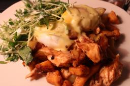poached eggs on salmon hash with hollandaise and sunflower shoots.