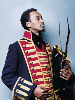 Somali-Canadian rapper K'naan's Muslim garb consists of wearing an 18th-century military uniform and a three-corner hat with some very, very long feathers.