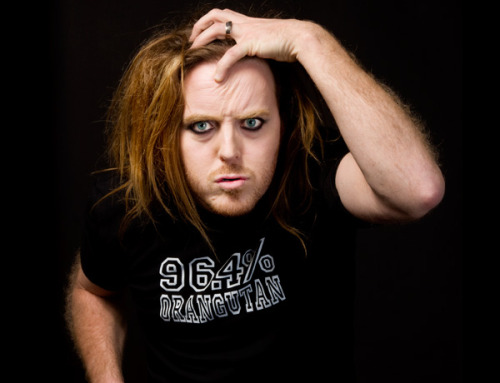 Tim Minchin wears a black T-Shirt with white text saying *96.4% orangutan* and mimes a rather simian pose