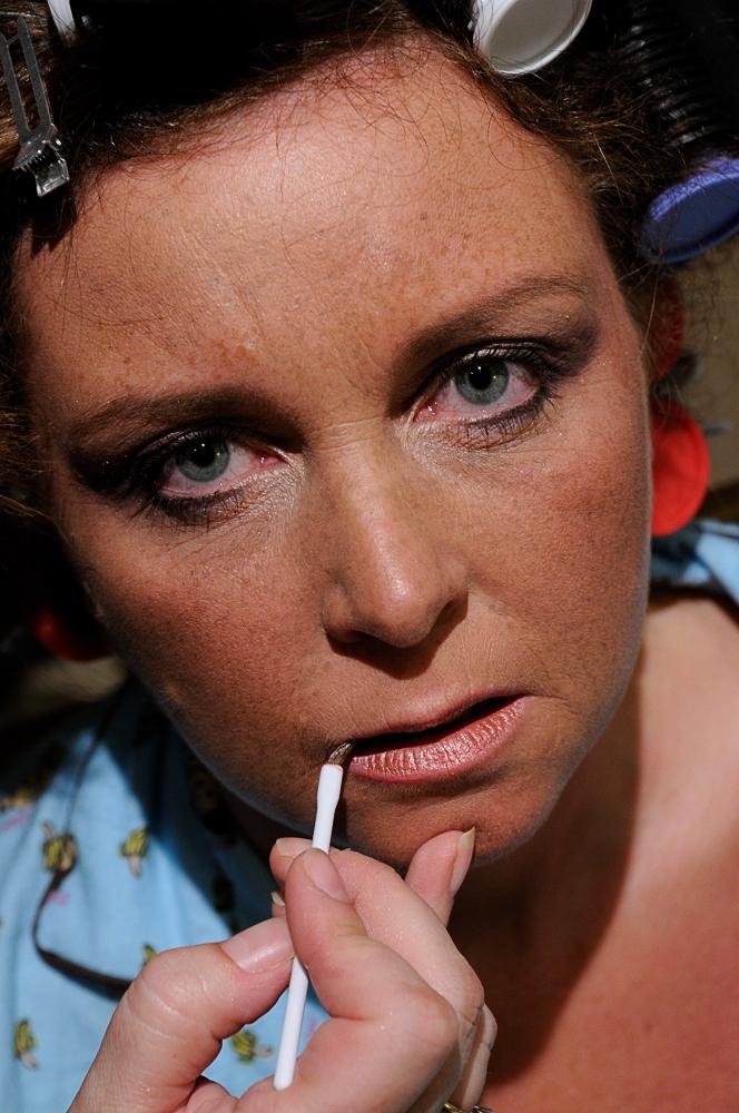 Carefully applying lipstick