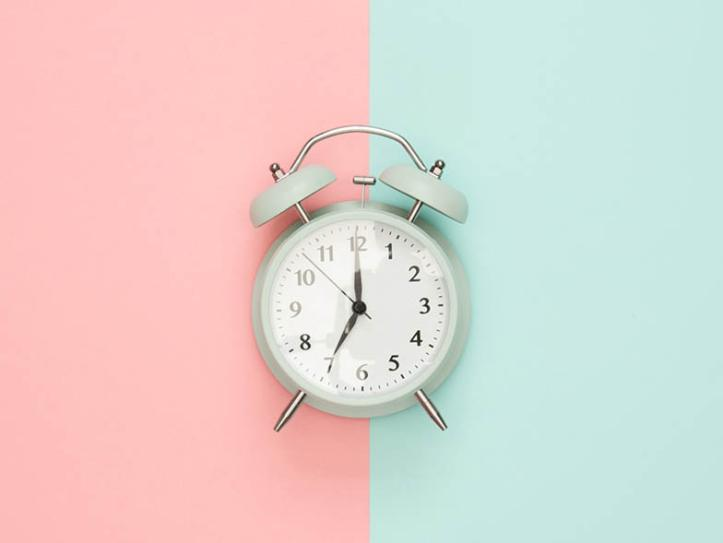 Teal alarm clock on pink and teal background