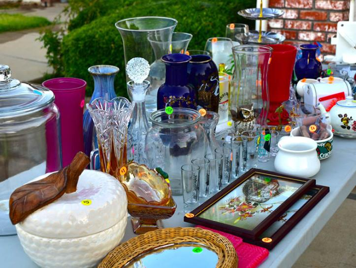 Yard sale items, mostly glassware, organized on a table