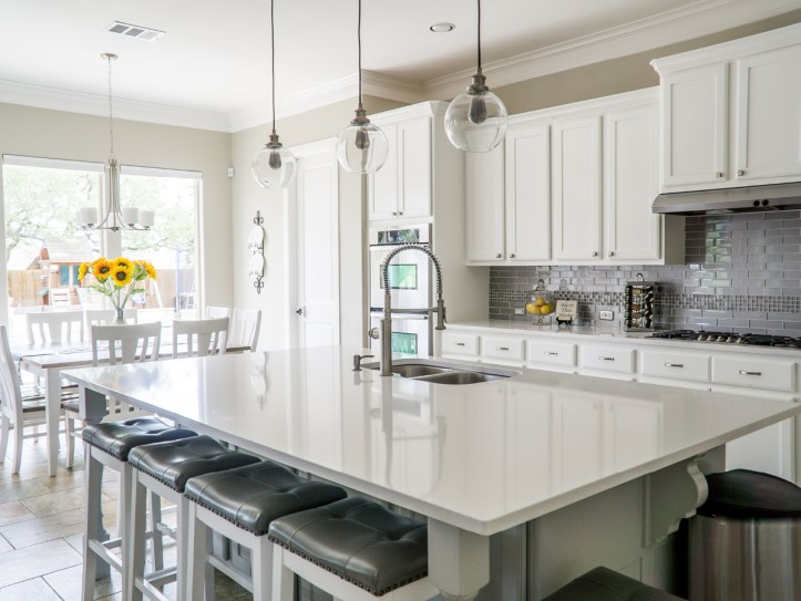 large white kitchen with white cabinets and hanging lights