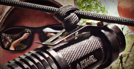 tying a knot to the clip of a firehawk flashlight