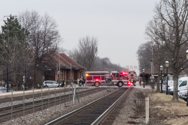 Fire engine crossing behind a Metra commuter in Riverside, Illionis