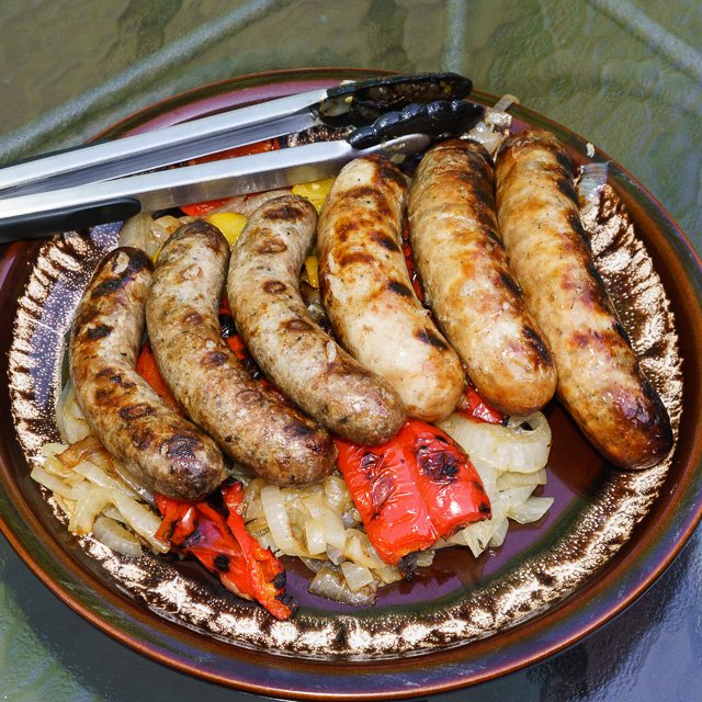 A platter of brats with onions and peppers