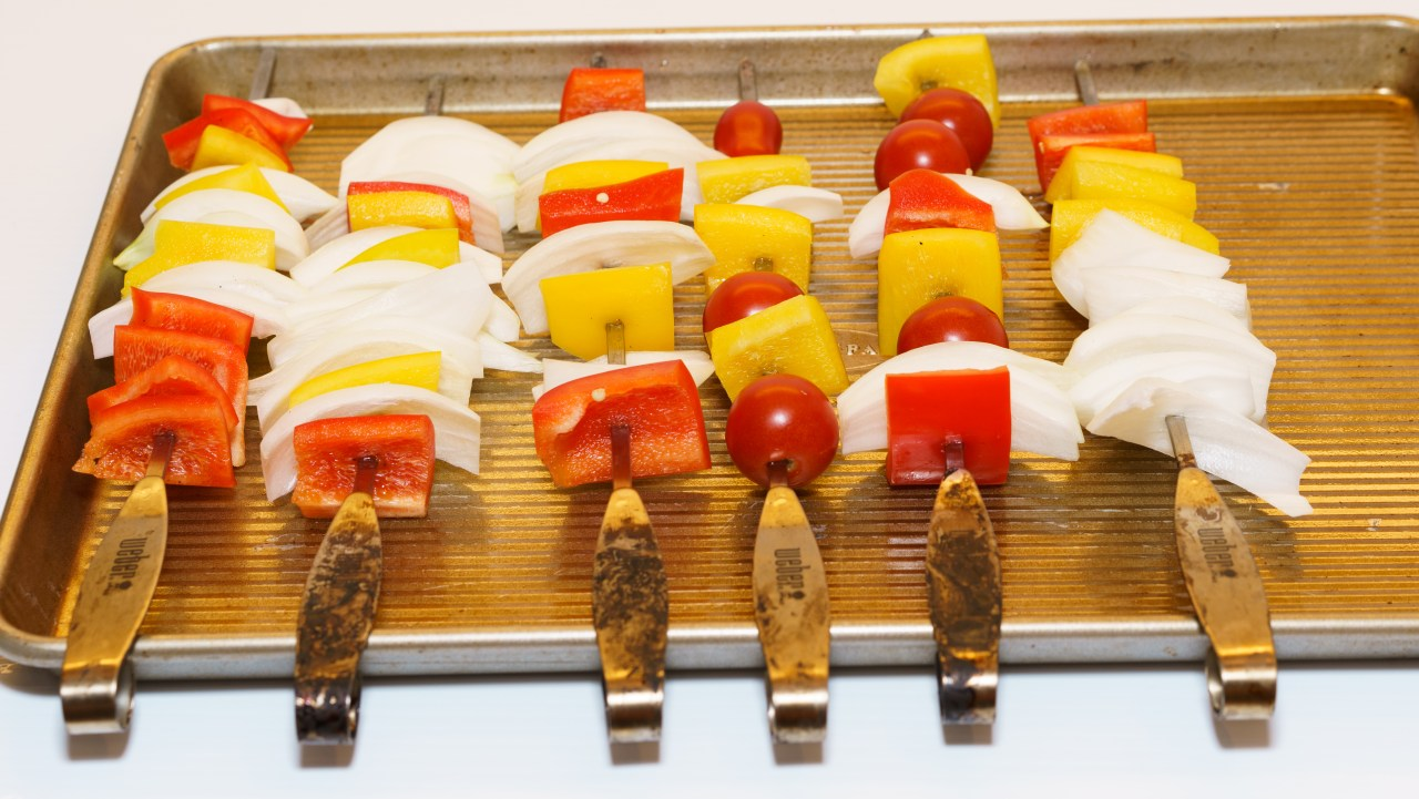 Peppers, onions, and tomato skewers ready for grilling