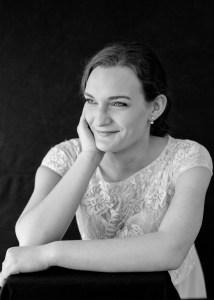 Side profile of Karina, smiling, leaning black background,