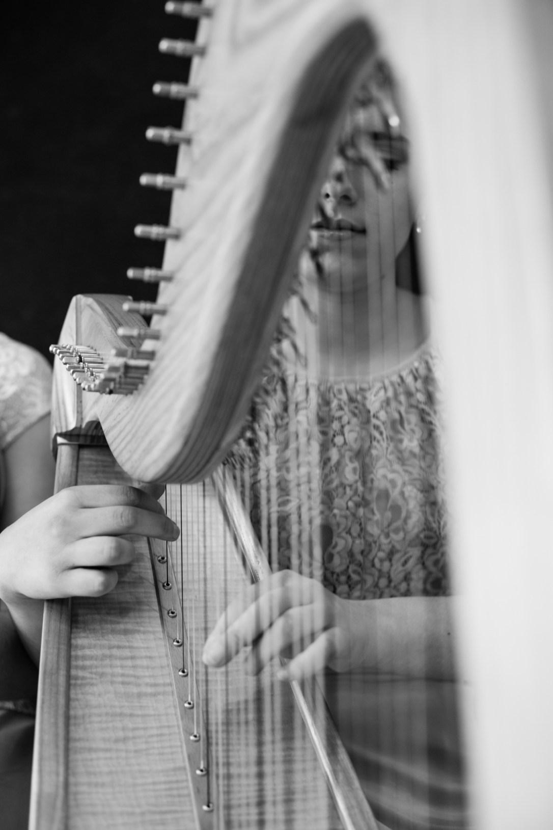 Close up of Adel, wedding harpist, looking through the strings, semi focus,