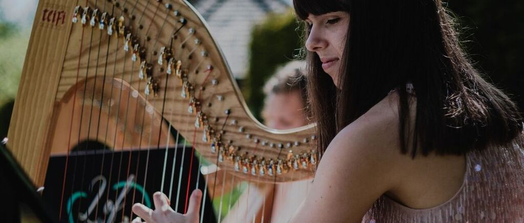 Close up of harpist performing at outdoor wedding ceremony, Swarling Manor Kent, 2 of Harps