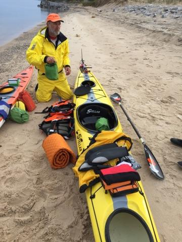 Loading a yellow Stellar kayak on the beach of Orchard Beach State Park, Michigan.