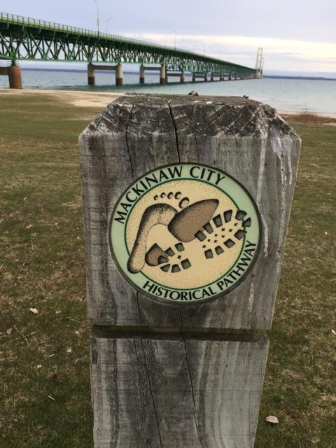 Mackinaw City Historical Pathway post sign facing bridge.