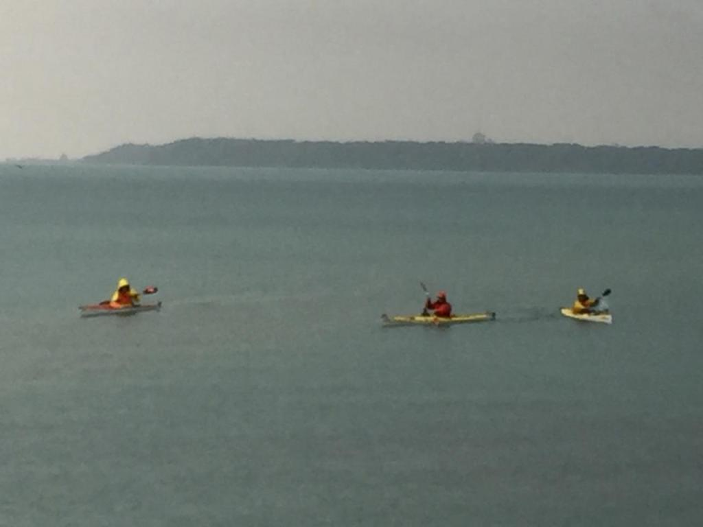 3 kayakers paddling by Klode Park.