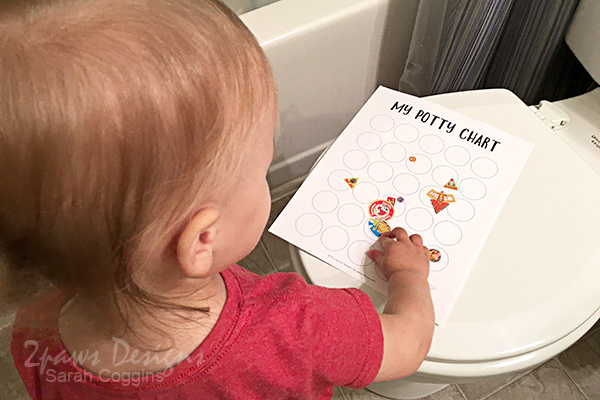 Toddler adding stickers to Potty Training Chart