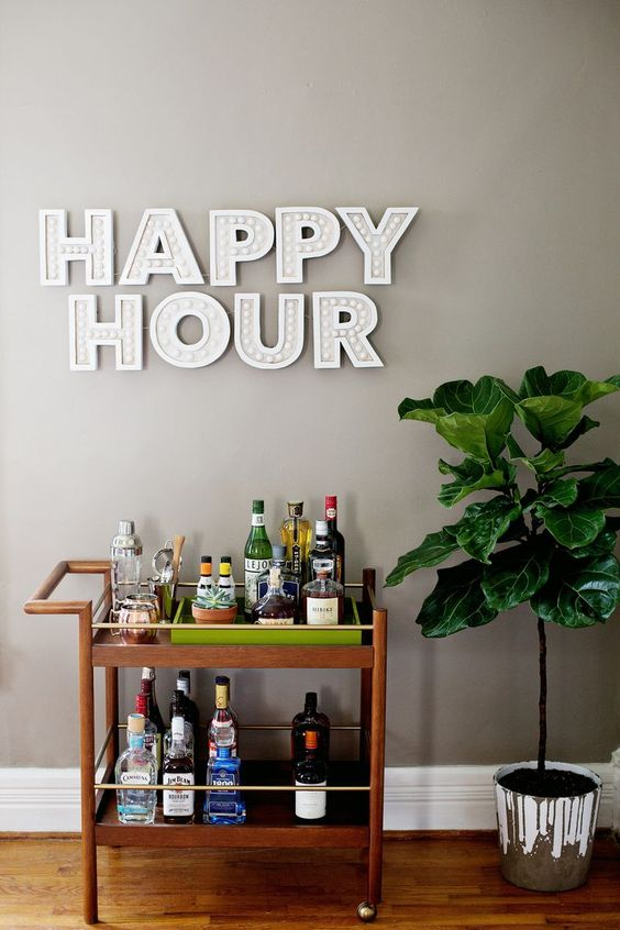 "Wooden bar cart with indoor potted floor plant beside and ""happy hour"" in decorative block text above"