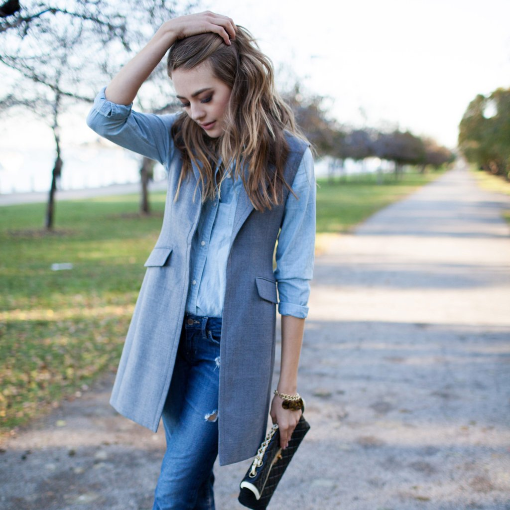 gray sleeveless vest with light blue button down and jeans for fall
