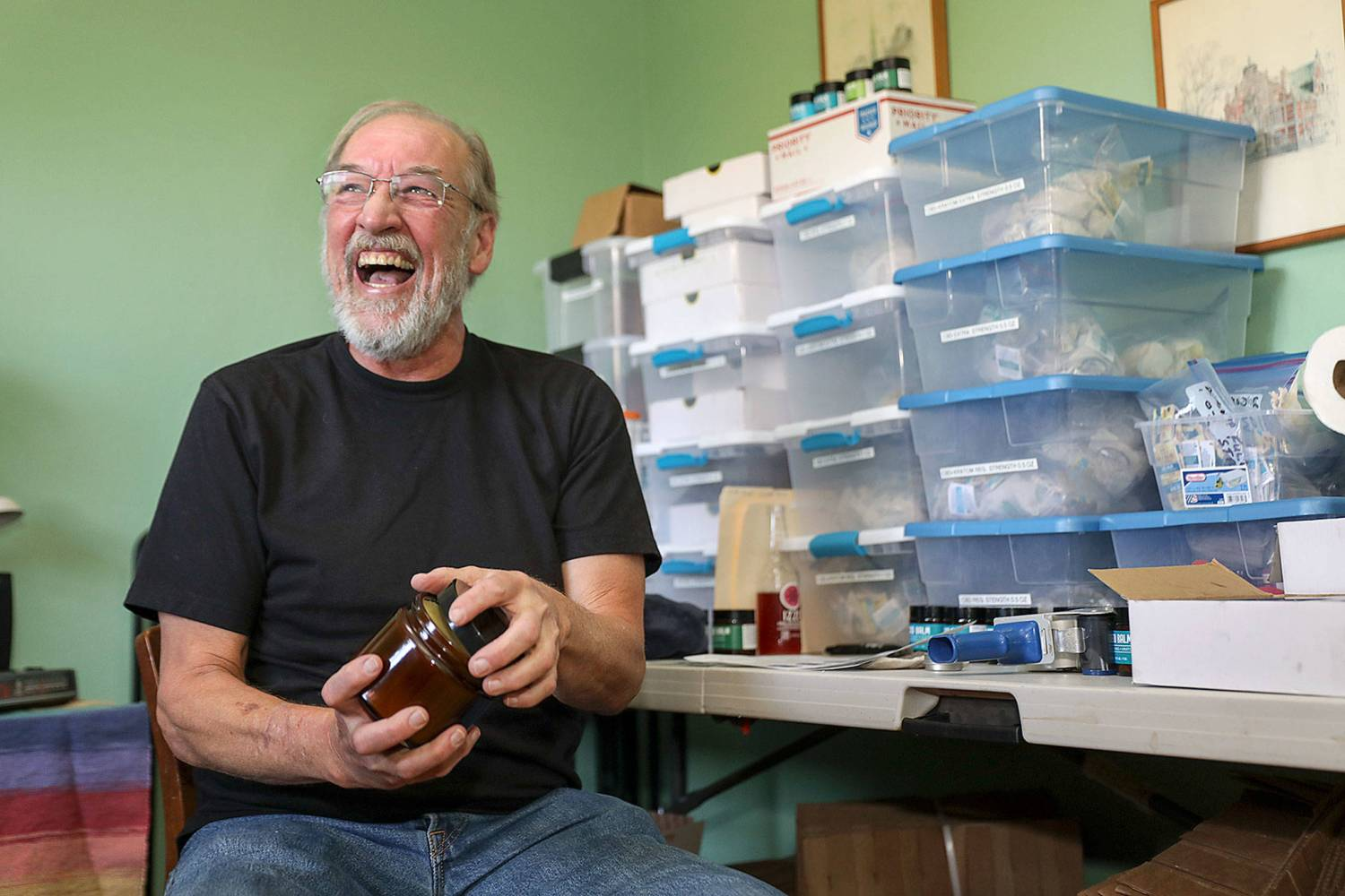 Ron Gordon, who worked as a carpenter for years, began using CBD topicals to relieve his body aches. Then he started making it and selling it online. He packs and ships it from the office in his Snohomish home, company headquarters for Ron's Balms & Botanicals. (Lizz Giordano / The Herald)