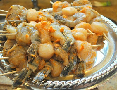 Shrimps and Scallops kabobs on a platter with marinade over them. by 2sistersrecipes.com