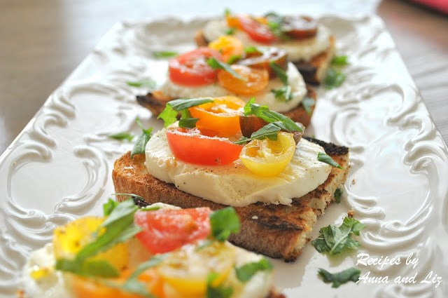 A long platter with Burrata Caprese Crostini Bites displayed by 2sistersrecipes.com
