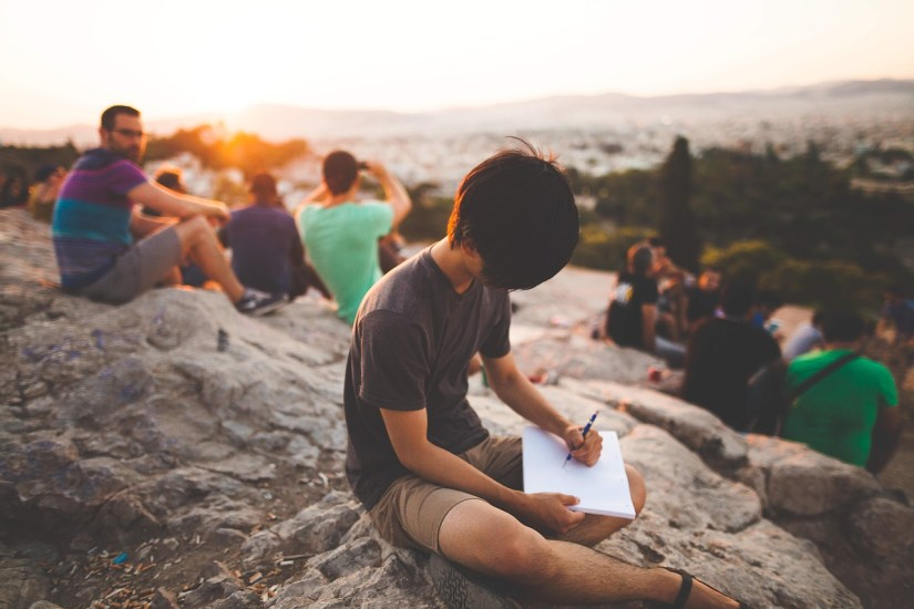 boy writing on a rock_StockSnap