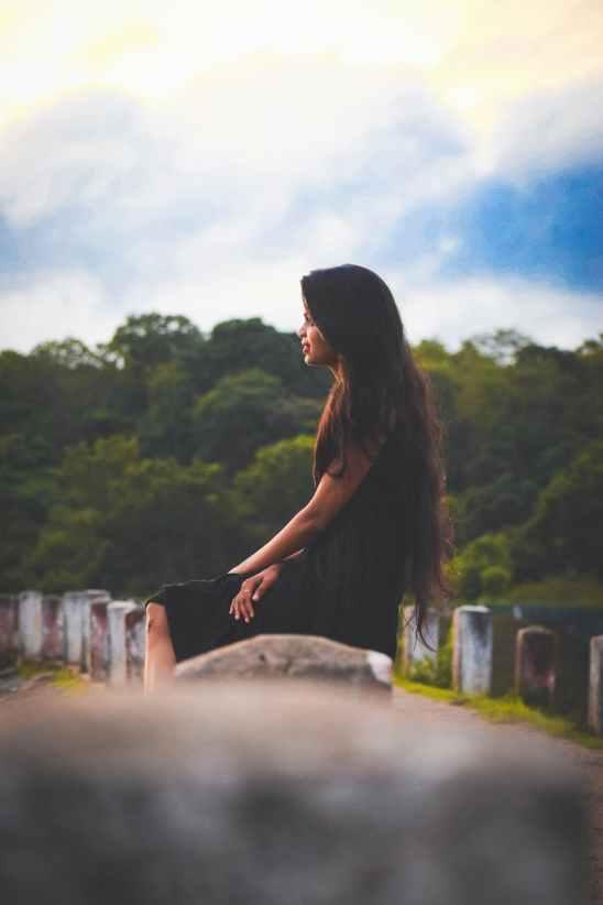 woman sitting on concrete pillar