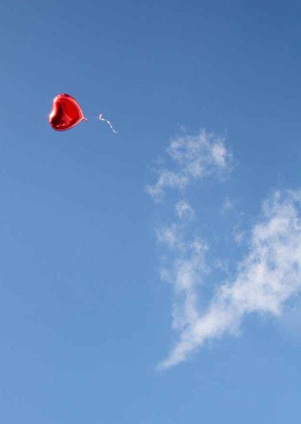 red heart shaped balloon in blue sky
