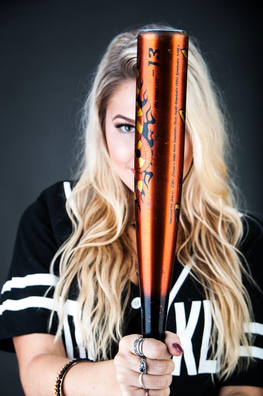 woman holding brown and black baseball bat
