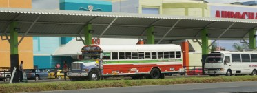 This is one of Panama's colorful buses. They are converted American school buses. The small white one behind is typical of the vans that are also part of the bussing system. The names of the cities that the vehicle services are on the top of the windshield