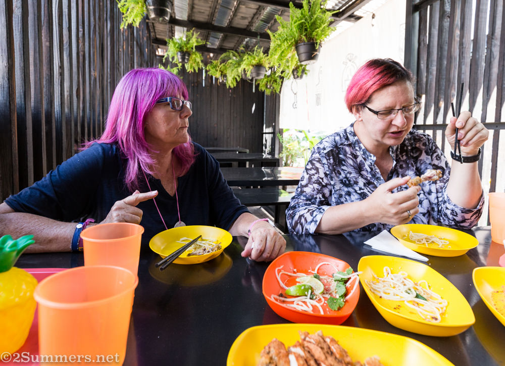 Pink-haired ladies eating chicken at Glory