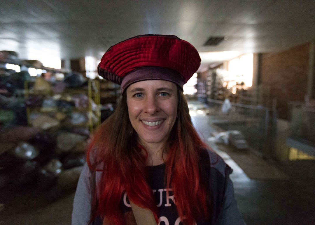 Heather wearing a red silk hat in Mabro Hats, an old hat factory in downtown Johannesburg.