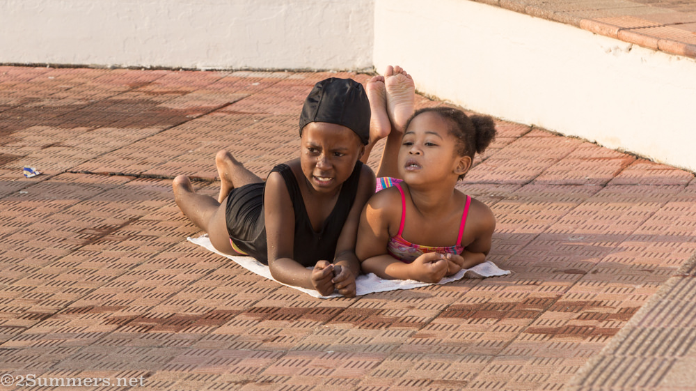 Little kids on towel at the pool
