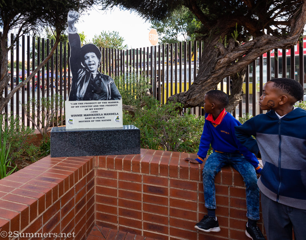 Kids in the Mandela House garden with a statue of Winnie Mandela