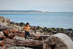 LittleMan walking on driftwood at Point Wilson Lighthouse Fort Worden Port Townsend 3