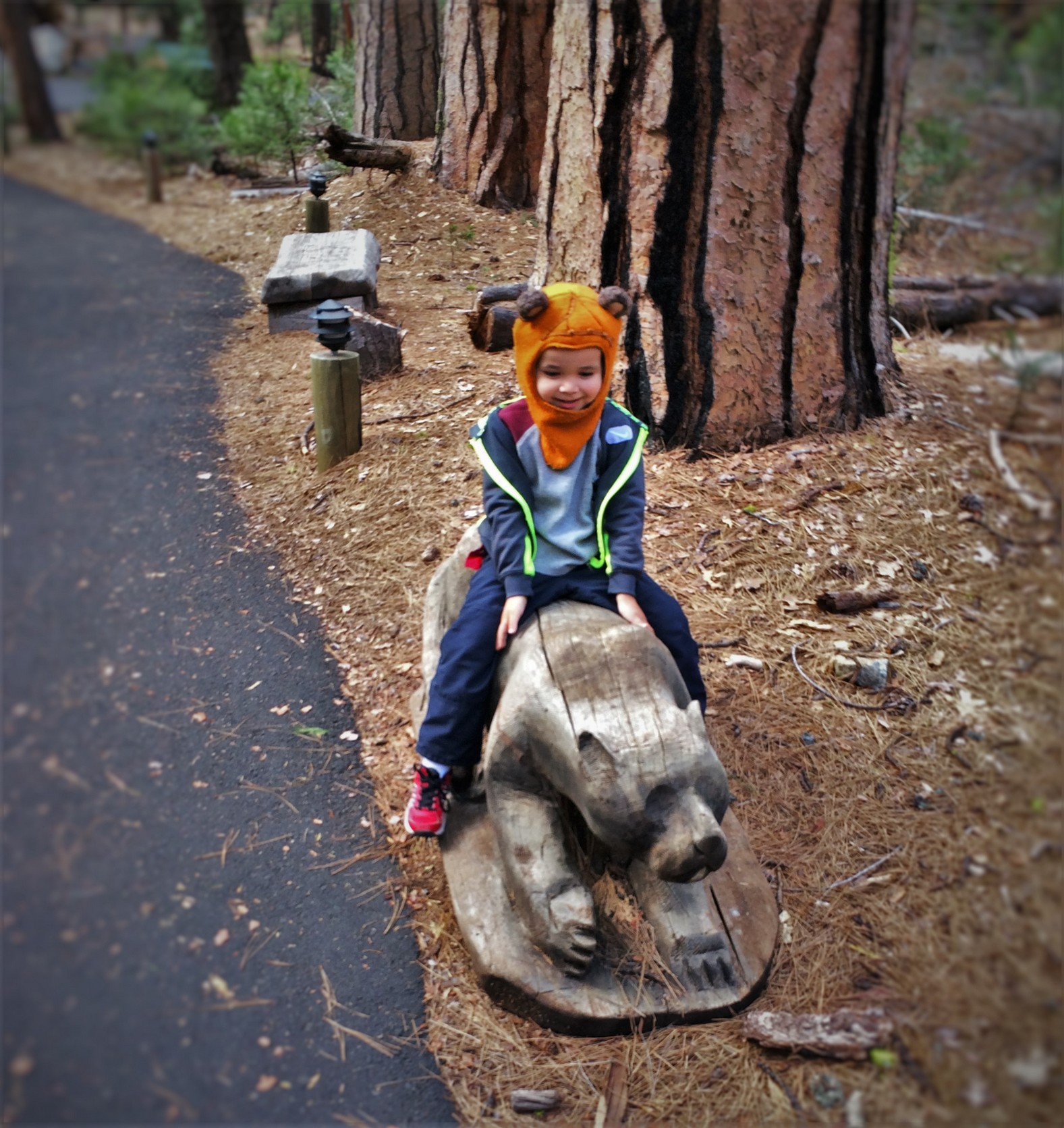 LittleMan riding carved bear at Evergreen Lodge at Yosemite National Park 1