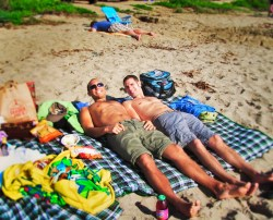 Taylors sun tanning at beach in Orange County