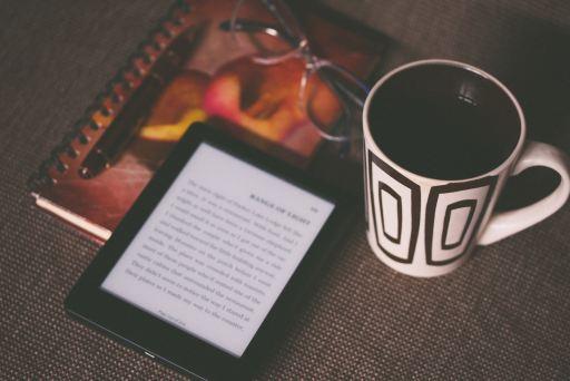 sortir mon premier ebook - Photo d'une liseuse et d'une tasse de café sur une table