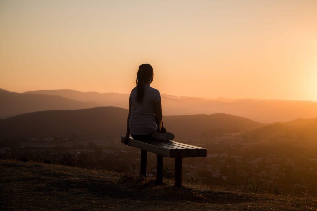 femme face à la montagne écoutant des podcasts