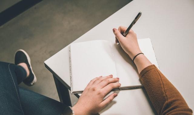Femme qui écris sur un cahier pour lâcher prise