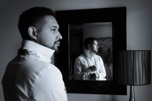 Homme mettant une chemise devant un miroir