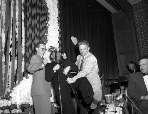 Even though at first hand this picture seems to show that the guy on the right loves holding the middle one's pole, this is actually  a photograph of Mayor A. W. Shackleford frozen to two microphones by a 50  volt shock caused by improper grounding.  Mayor Shackleford was just about to introduce Teen Queen Donna Glock and  runner-up Shirley Parkinson at a Valentine Dance, 1953, when he grabbed  both microphones. Because the wires were improperly grounded the  current flowed into the Mayor's body and froze his hands to the  microphones until the power was turned off.  Poor Mayor. source