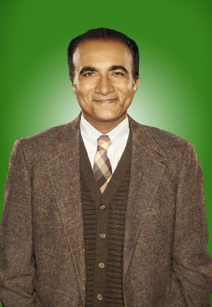 Principal Figgins, played by Muslim actor Iqbal Theba, is wearing a smirk because he just figured out how to get out of Sue Sylvester's blackmailing. For now…