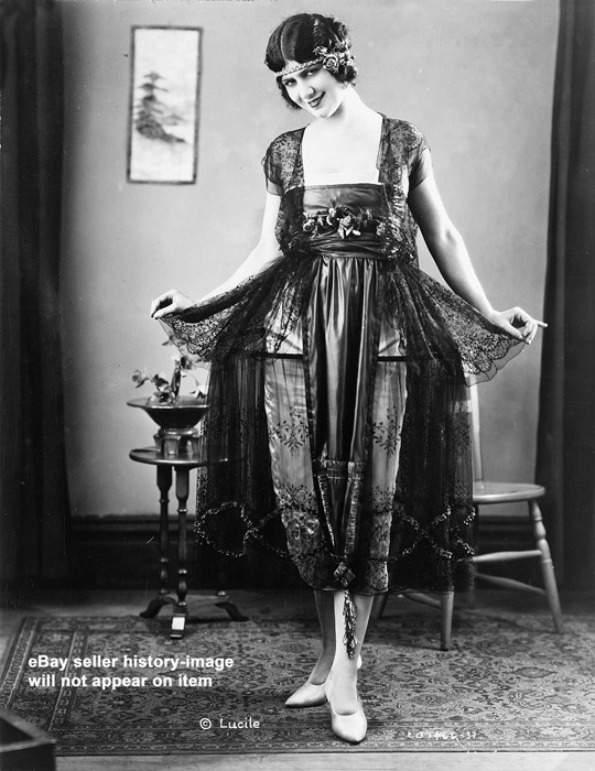 1921 Lucile evening gown of a black chantilly lace hoop over a white satin slip, shown at the National Retail Garment Association Fashion Show at the Hotel Commodore, NYC. From Ebay.