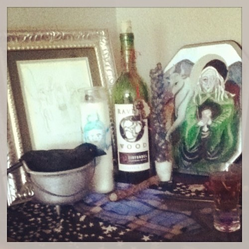 How to set up an altar. If you are like me, and are a witch that works with gods or other powers, you might want to have an altar or two in you living space. This is a space you will do your witchery and chill with the spirits or deities you prefer. But for some reason, altars tend to be intimidating! You see other witches' altars and its just like, OH GODS I DON'T HAVE STUFF!!! Look, you probably do have stuff, you just don't realize how nice it might look together and how meaningful it could be for you and your powers. So let me help you out from the ground up. First colors—a pretty altar has some color coordination. Pick one piece that has a few different colors in it for your anchor to the altar. Determine what color family it is in. Spring, Summer, Fall, or Winter Colors? What is this starting piece? It might be a work of art. I have used framed greeting cards, post cards, and small print offs from my computer for my altars—and I have painted, collaged and drawn my own, most anything looks good framed. You can use a frame you already have, buy one at a discount store, or make one out of stuff you have like construction paper or wrapping paper. Another good piece that might have a few colors is a scarf that you can use as an altar cloth. Once you have a color scheme, pick out other things that look good color and pattern wise with your main piece. You might have another scarf that is a complimenting or matching shade or even some lace that you can layer with your other altar cloth. Often some sort of dishes end up on an altar, a plate, bowl or cup of some kind for offerings. If you have one or more of these, make sure they look good together. You can go for a matching set, or go for the funky mismatched look, as long as the colors and patterns seem to work out together. I used a glass shot glass and a small cheap cauldron and crow decoration from Halloween. Many altars have candles and along with that candle holders. You can go as simple as a little tea light on