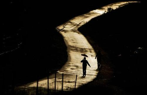 A Palestinian holds an umbrella as he walks along a deserted road during a rainy day in the West Bank city of Ramallah, Tuesday, March 24, 2009. (Muhammed Muheisen / AP)